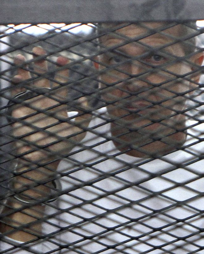 Al Jazeera journalist Peter Greste of Australia stands in a metal cage during his trial in a court in Cairo