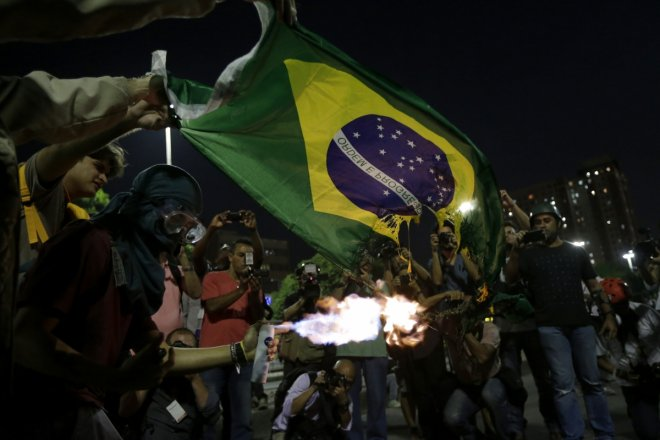 Demonstrators burn a Brazilian flag during a protest against the 2014 World Cup in Rio de Janeiro