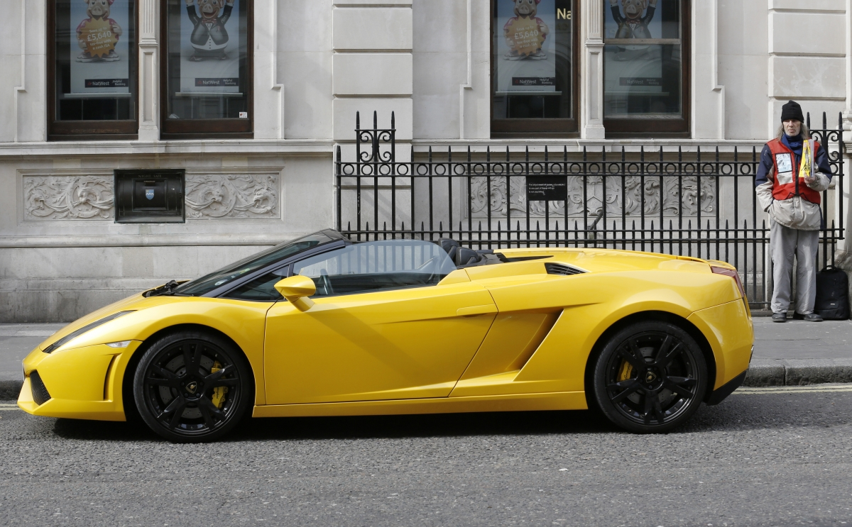 A homeless man sells a copy of The Big Issue nest to a Lamborghini sports car in central London. (Reuters)