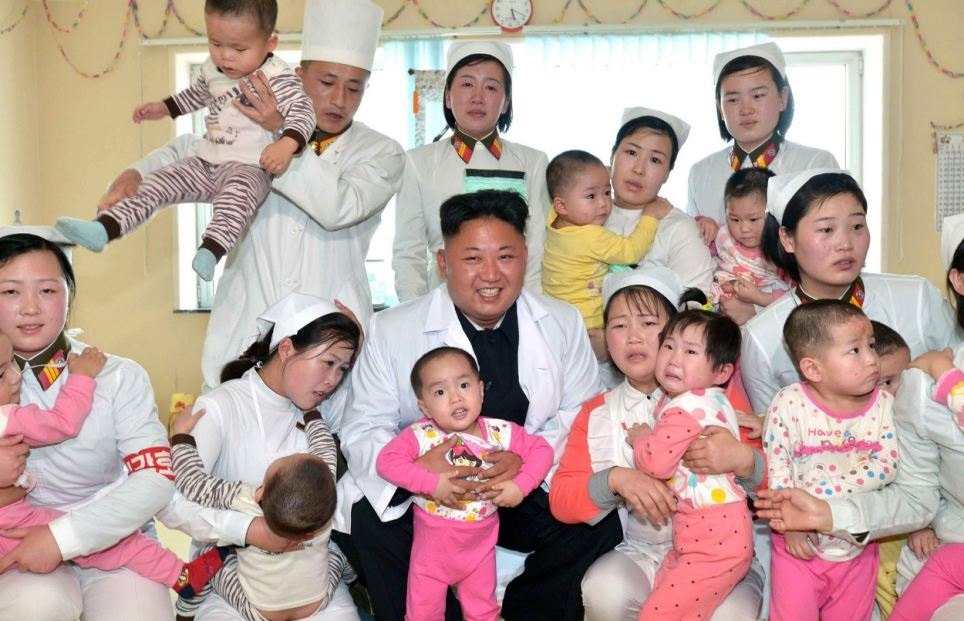 Kim Jung Un poses with (presumably) loyal young pioneers following apartment block collapse disaster