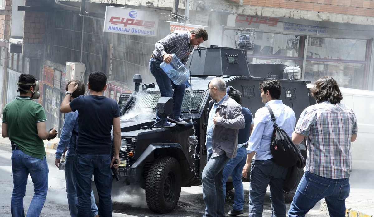 A man pours water on an armoured police vehicle after it was set on fire by fire bombs during clashes between protesters and riot police in Istanbul