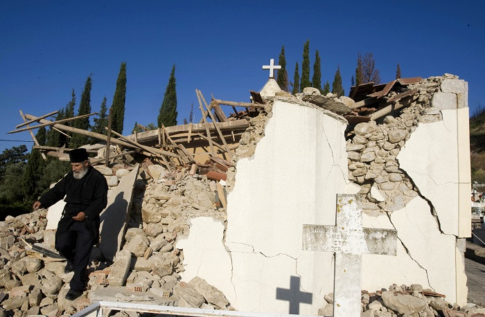An Orthodox priest walks on the debris of a church of Valmi village, south-west of Athens.