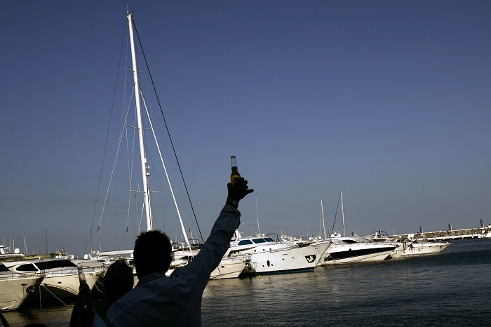 Tourists drink beer at the popular holiday resort of Puerto Banus on the Costa del Sol in southern Spain.
