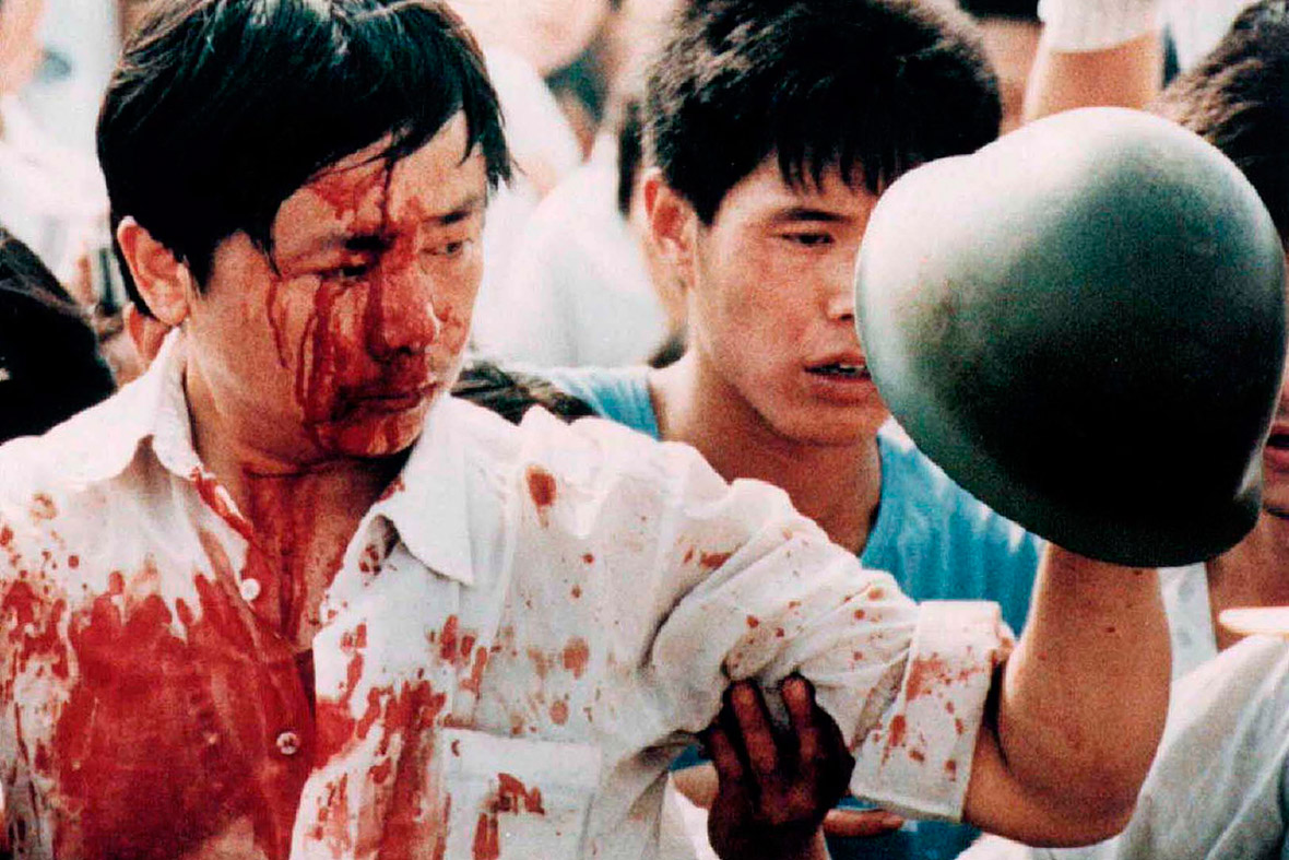 4 June 1989 A blood-covered protester holds a Chinese soldiers helmet following violent clashes with military forces during the pro-democracy demonstrations in Tiananmen Square