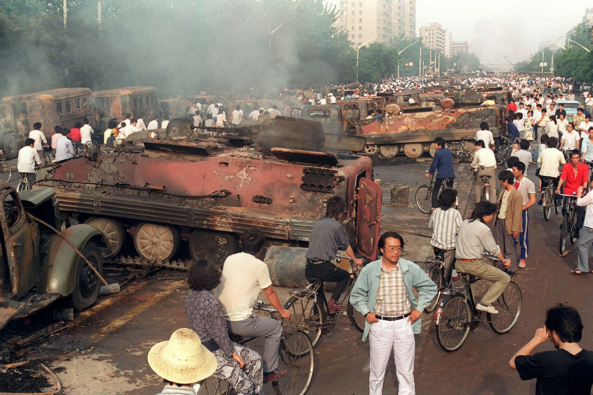 4 June 1989 Beijing residents inspect APCs burnt by demonstrators to stop troops moving into Tiananmen Square