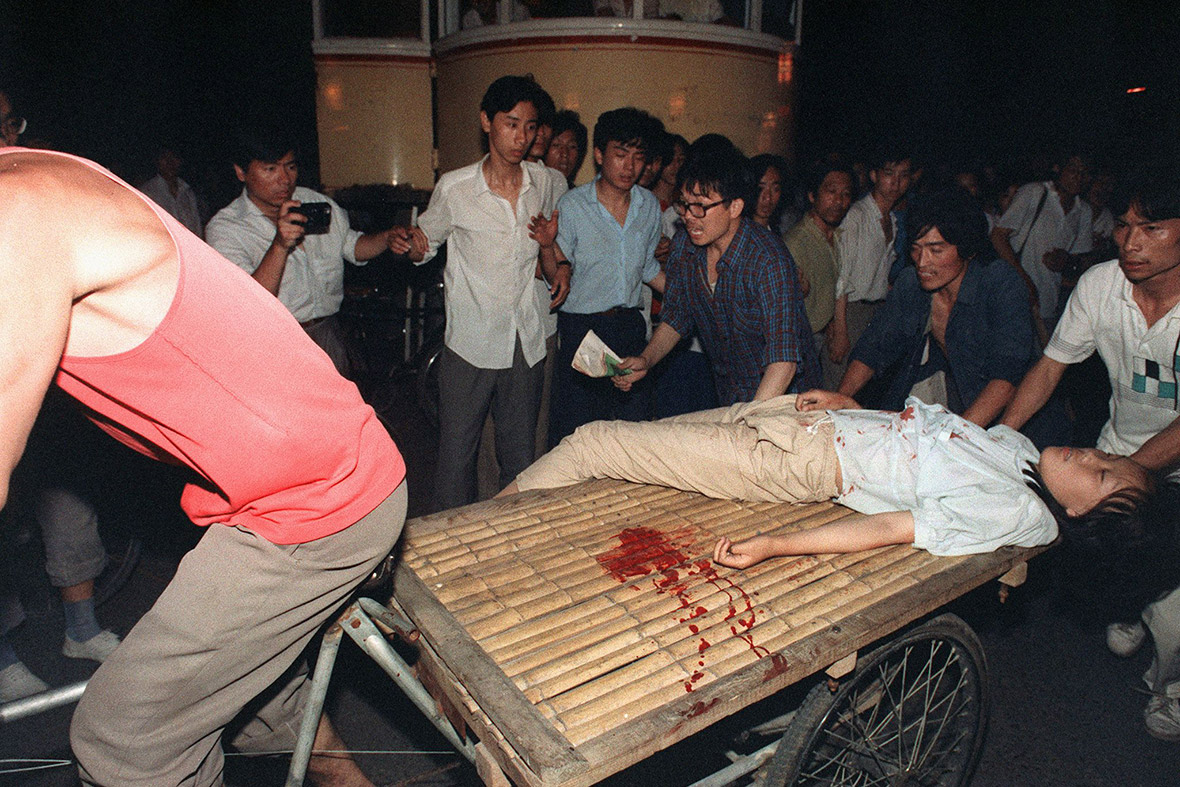 4 June 1989 A girl wounded during clashes between the army and students near Tiananmen Square is carried out on a cart