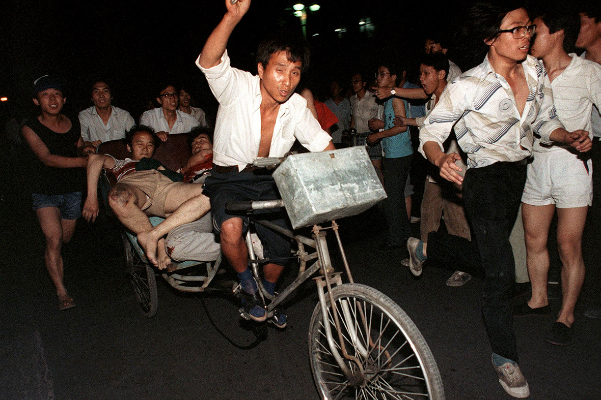 4 June 1989 Two injured people are carried out of the square on a bike