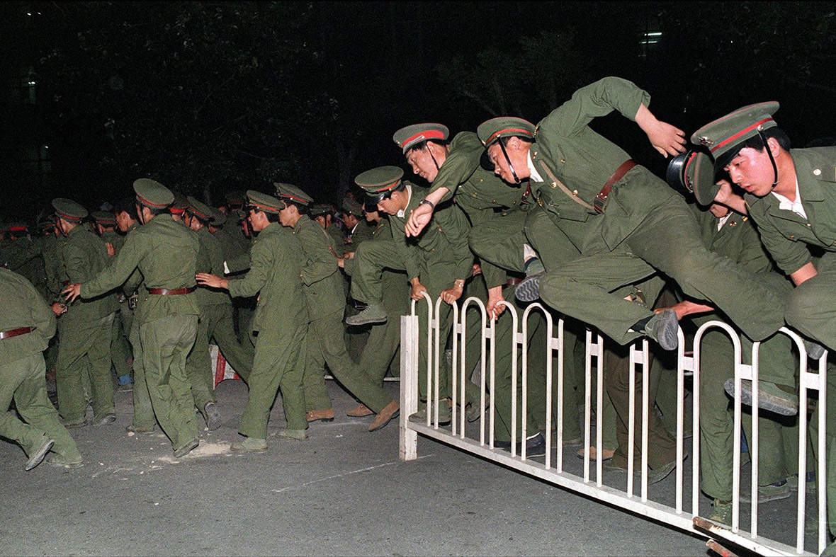 4 June 1989 Peoples Liberation Army soldiers leap over a barrier on Tiananmen Square as troops forcibly end the occupation by student protesters by using lethal force