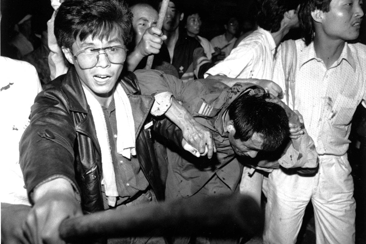 4 June, 1989 Students help a a captured tank driver to safety as the crowd beats him