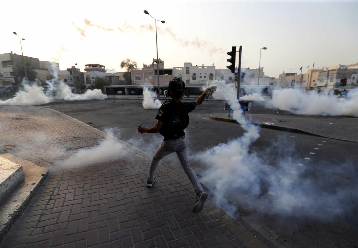 An anti-government protester throws back a tear-gas canister that was fired by the police as they clash during a funeral procession