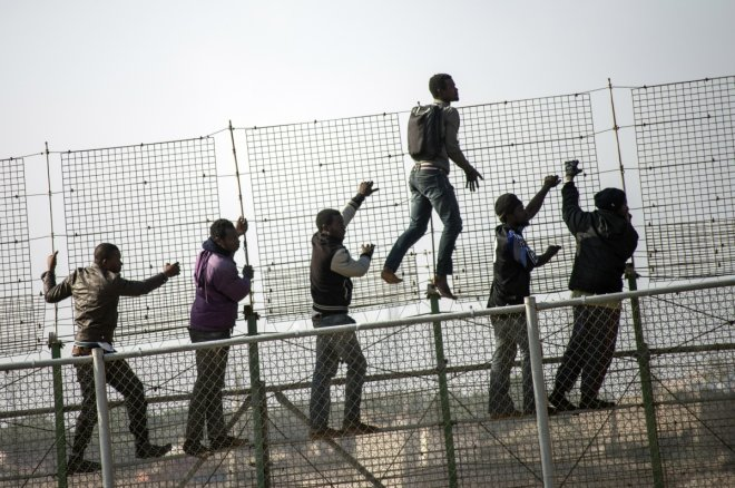 African migrants climb a border fence covered in razor wire during their latest attempt to cross into Spanish territory between Morocco and Spain's north African enclave of Melilla