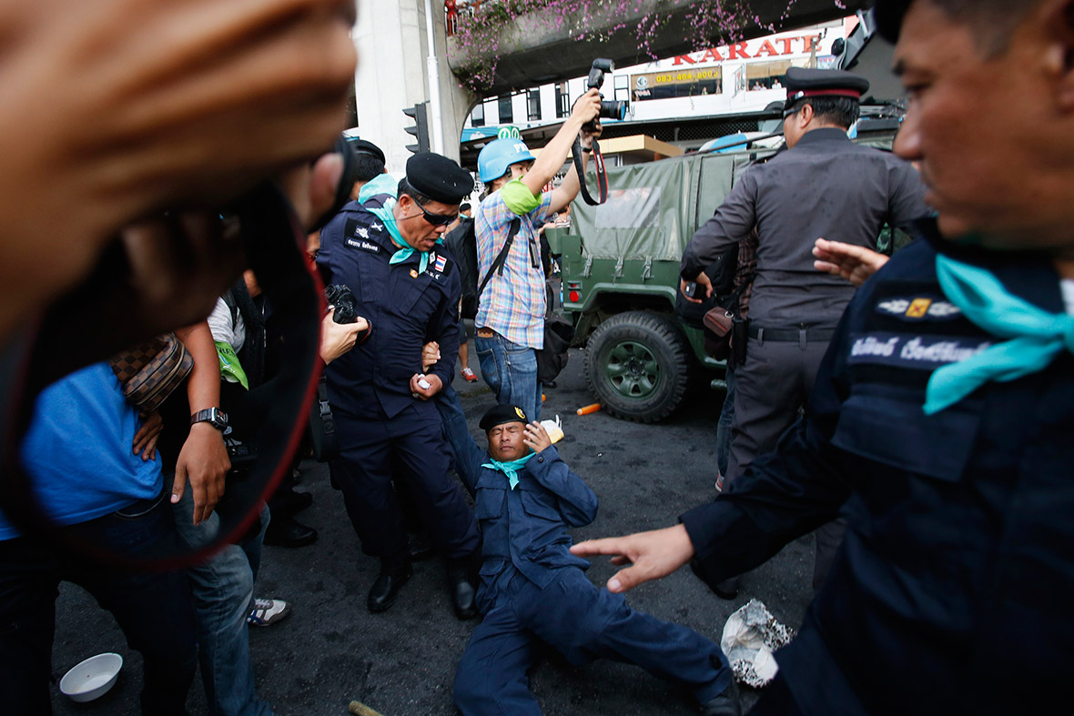 A policeman is knocked to the ground after being hit by a rock during a fight with demonstrators protesting against the Thai coup