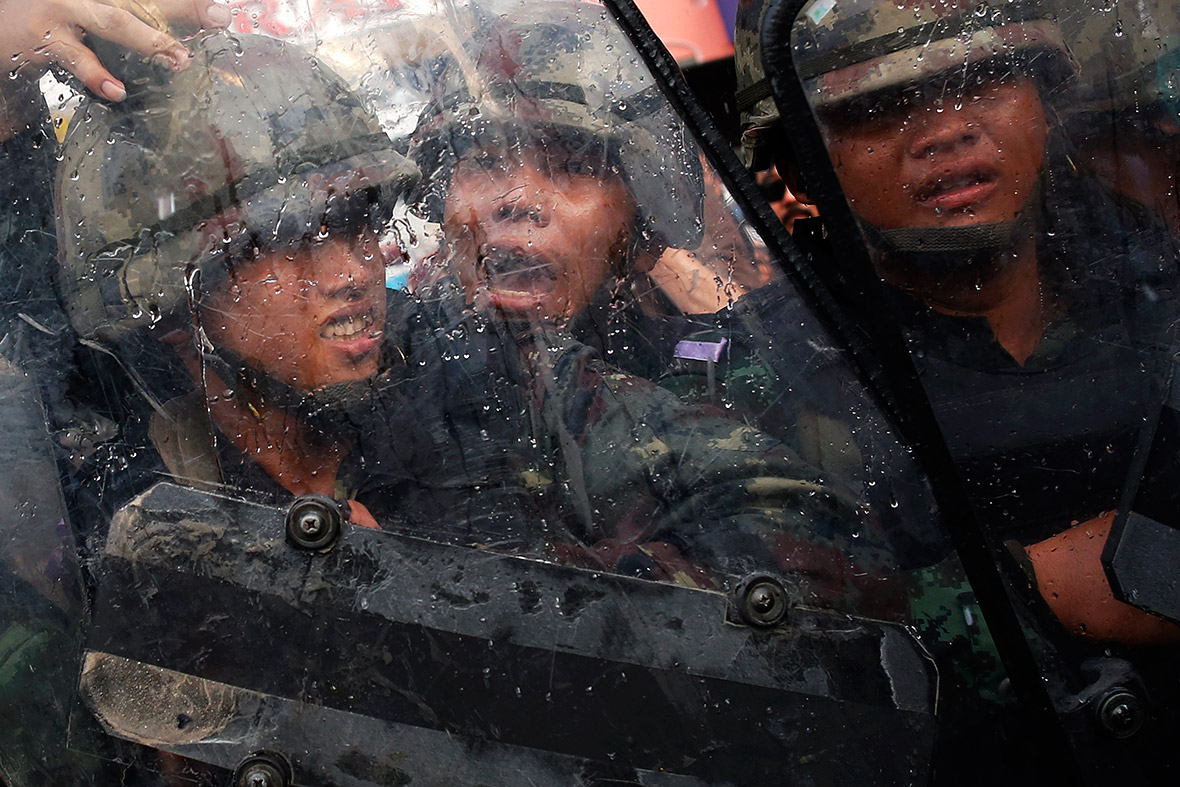 Thai Army soldiers protect themselves with shields as objects are thrown at them during a confrontation with anti-coup protesters at Victory Monument, Bangkok