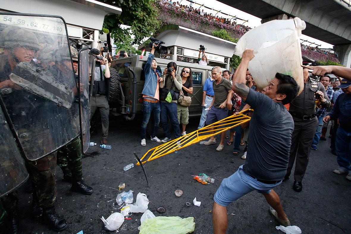 A protester throws a rubbish bin at soldiers during a scuffle at the Victory Monument, Bangkok