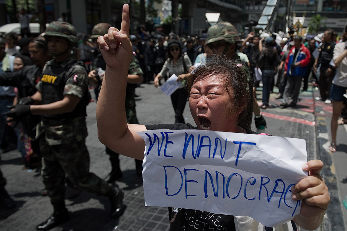 Thai soldiers walk past anti-coup protesters during a planned gathering in Bangkok