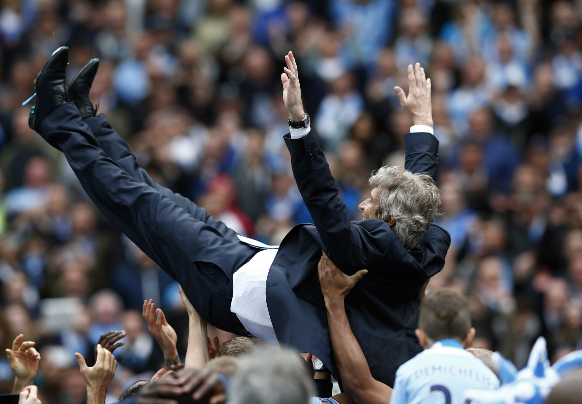 Manchester City\'s manager Manuel Pellegrini is thrown into the air by his team as they celebrate winning the English Premier League trophy following their soccer match against West Ham United at the Etihad Stadium in Manchester, northern England May 11,
