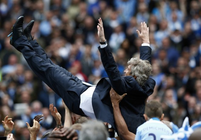 Manchester City's manager Manuel Pellegrini is thrown into the air by his team as they celebrate winning the English Premier League trophy following their soccer match against West Ham United at the Etihad Stadium in Manchester, northern England May 11,