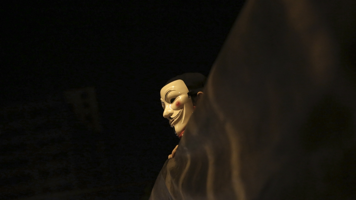 A demonstrator of the group called Black Bloc wears an anonymous mask as he holds a banner during a protest  in Sao Paulo
