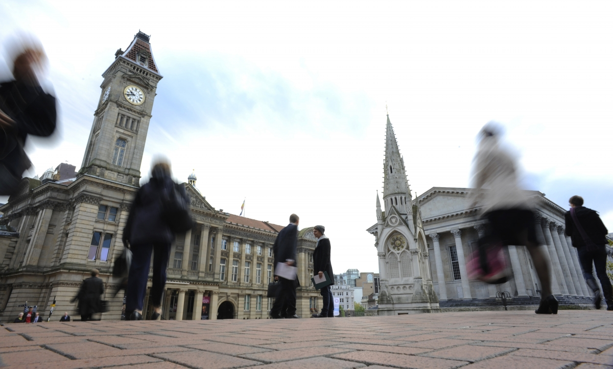 Commuters pass the Town Hall and Council House in Birmingham in central England