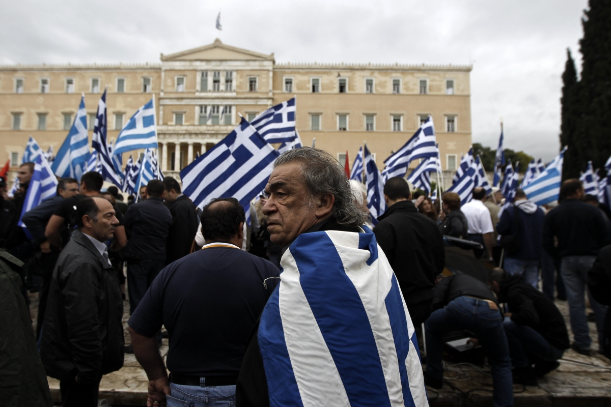 A supporter of Greece's far-right Golden Dawn wears a national flag on his back during a rally in front of the Greek Parliament in Athens