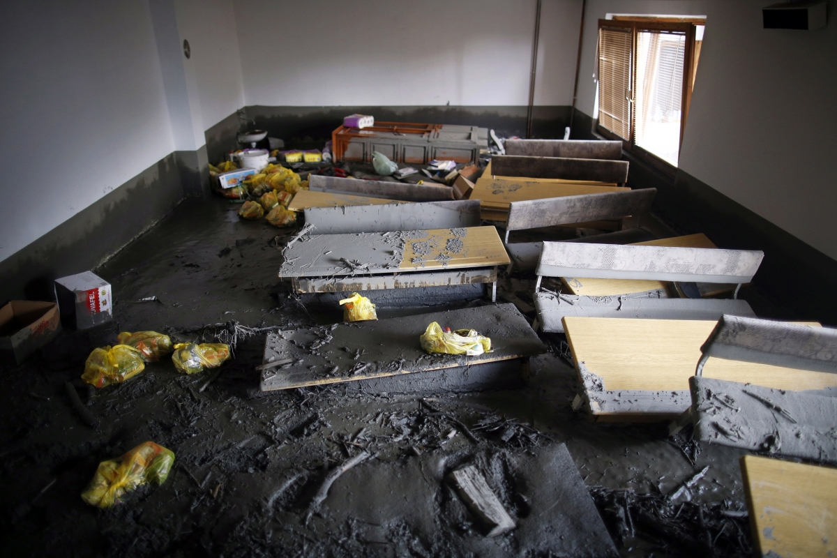 Mud covers a classroom and benches of a school in the aftermath of floods in Topcic Polje