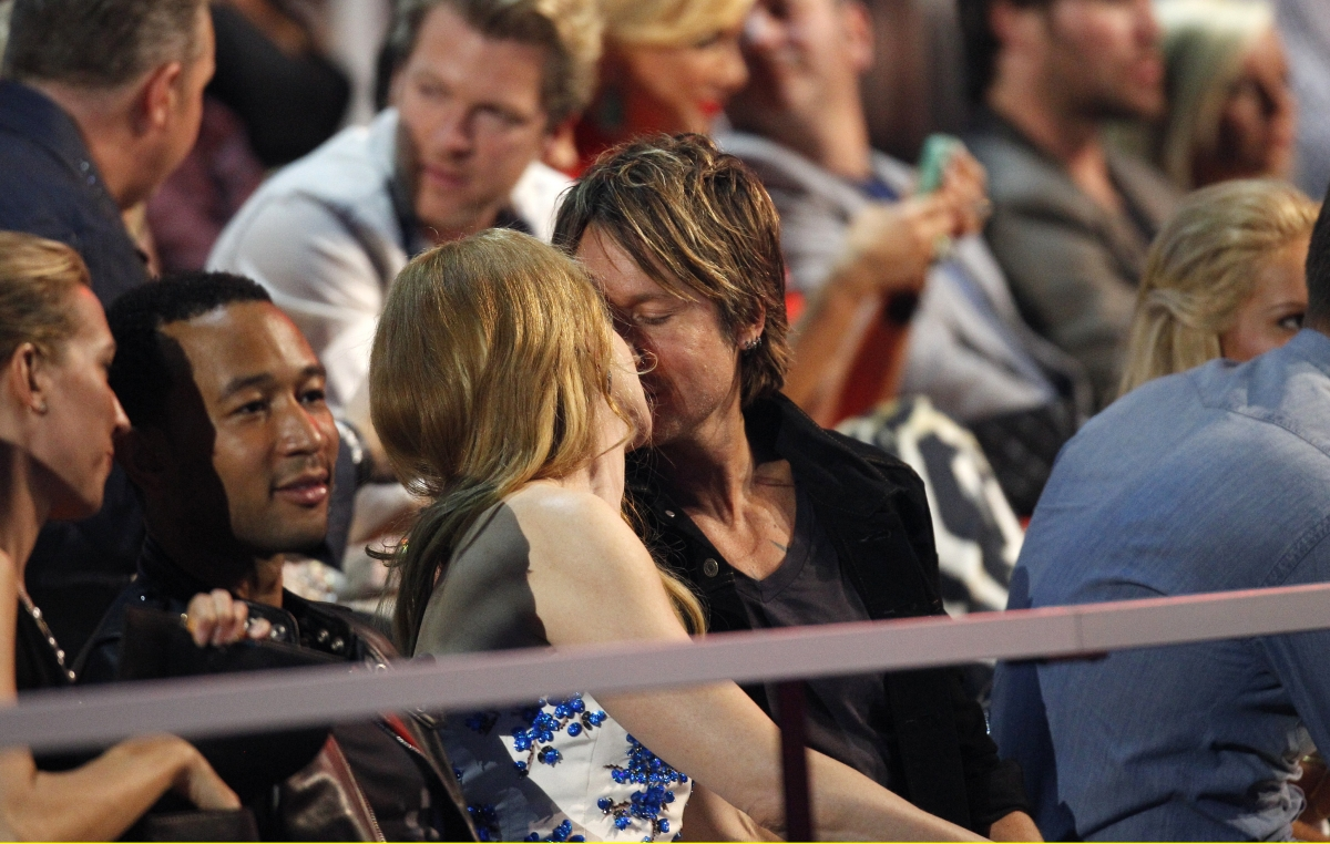 Nicole Kidman and husband Keith Urban kiss in the audience as musician John Legend (L) sits nearby during the 2014 CMT Music Awards in Nashville, Tennessee.