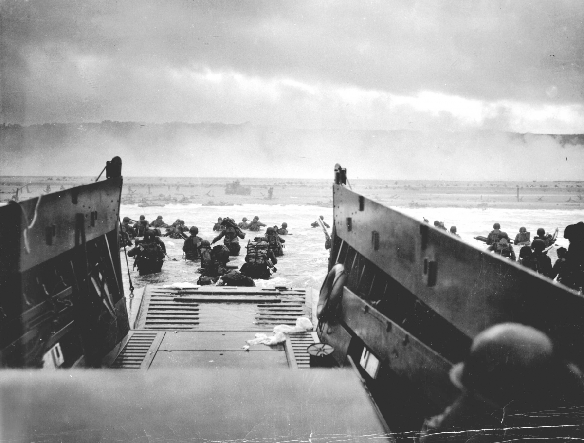 US troops wade ashore from a Coast Guard landing craft at Omaha Beach during the Normandy D-Day landings near Vierville sur Mer, France, on June 6, 1944