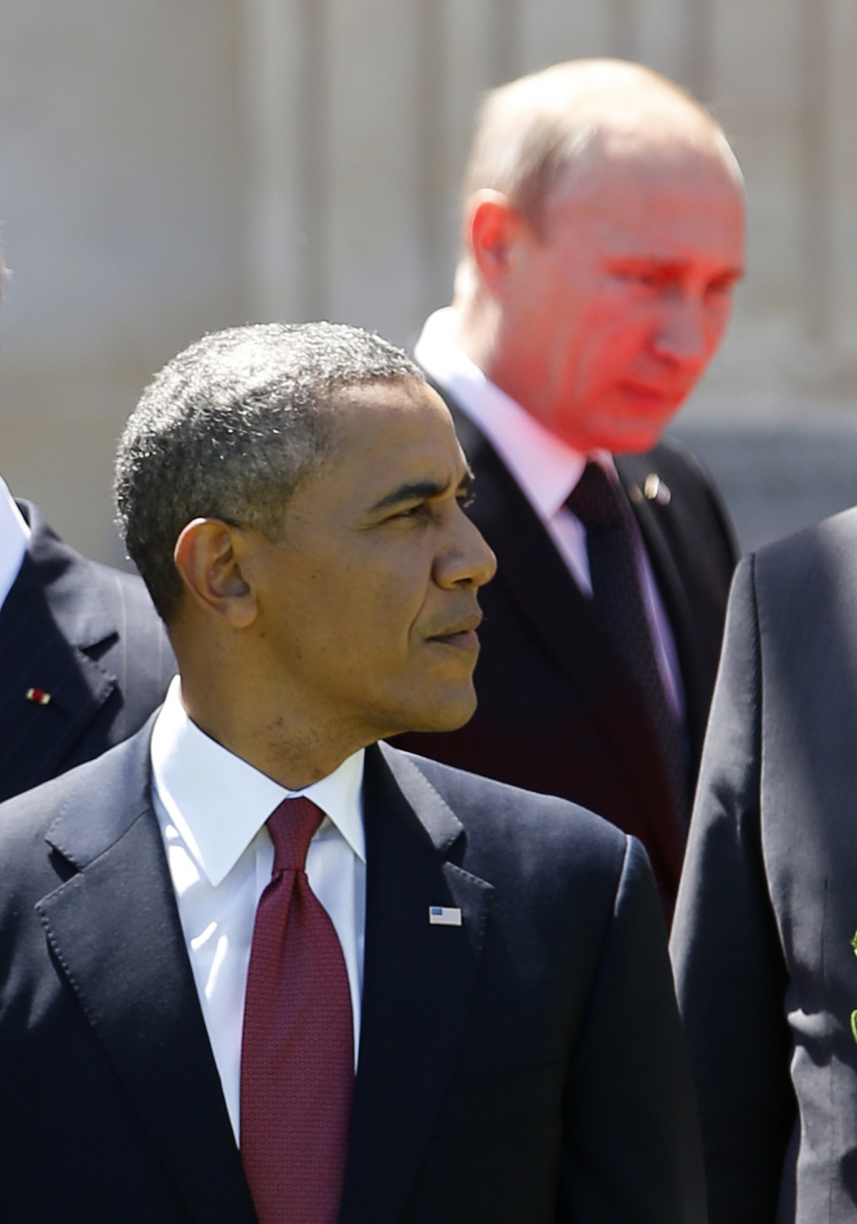 Red light reflected from the carpet illuminates Russian President Vladimir Putin as he passes U.S. President Barack Obama at a group photo for the 70th anniversary of the D-Day landings in Benouville