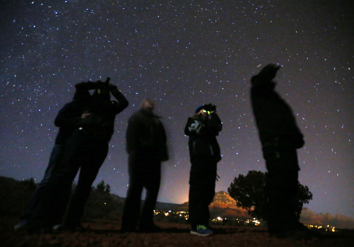 People use night vision goggles to look at the night sky during an Unidentified Flying Object (UFO) tour