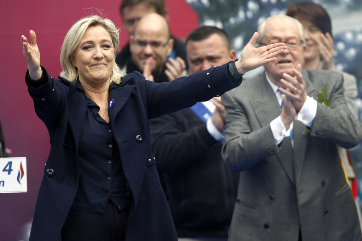 France's far right National Front political party leader Marine Le Pen (L) gestures at supporters next to her father Jean-Marie Le Pen
