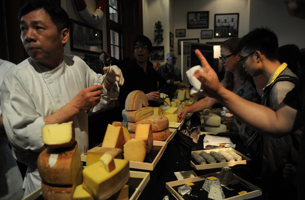 Chinese people sampling cheese at a market.
