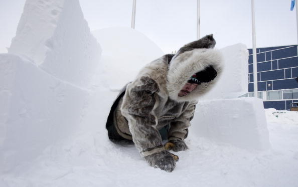 Inuit hunter Pitseolak Alainga crawls out of an igloo in Iqaluit, Canada