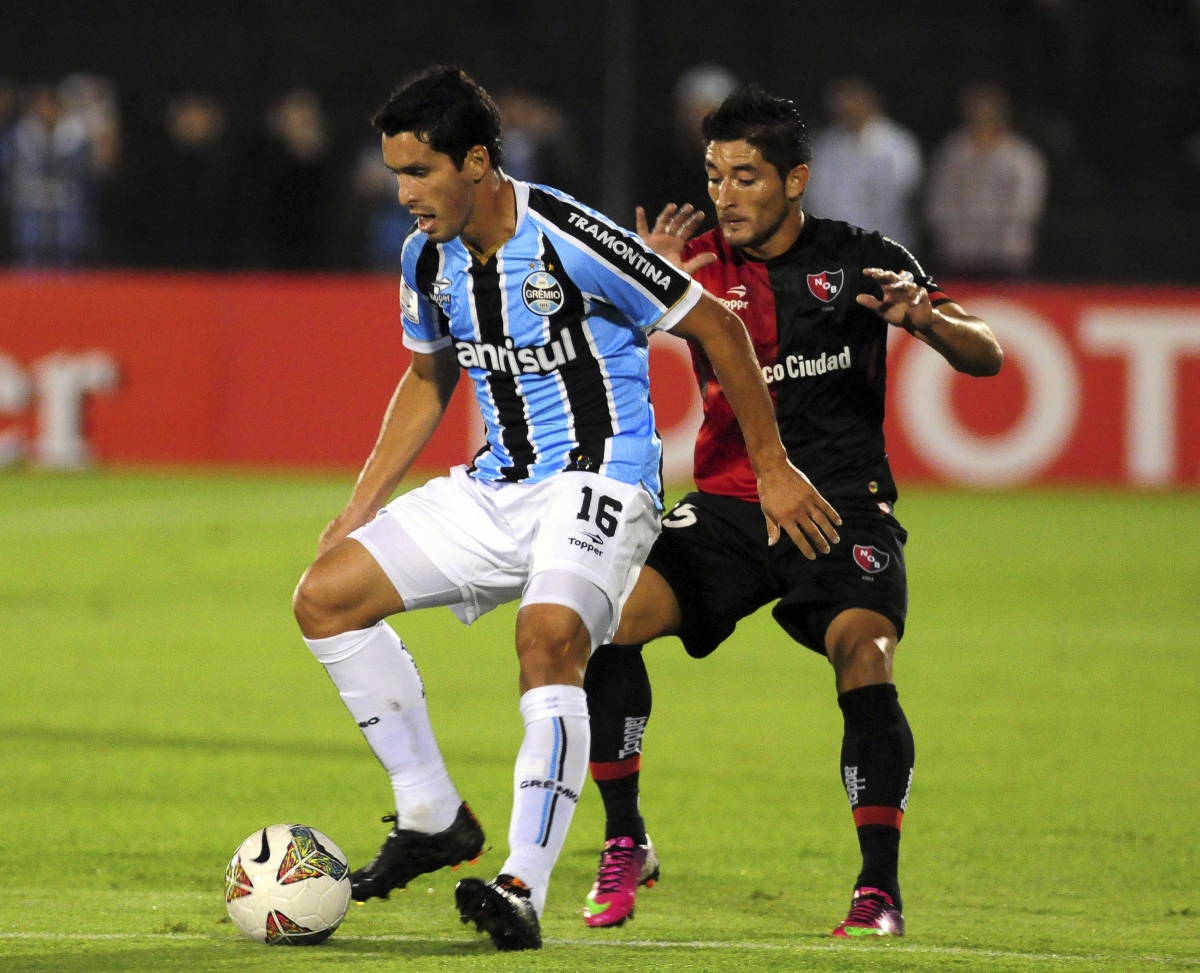 Milton Casco of Argentina's Newell's Old Boys (R) challenges Bressan of Brazil's Gremio during their Copa Libertadores soccer match in Rosario March 19, 2014.