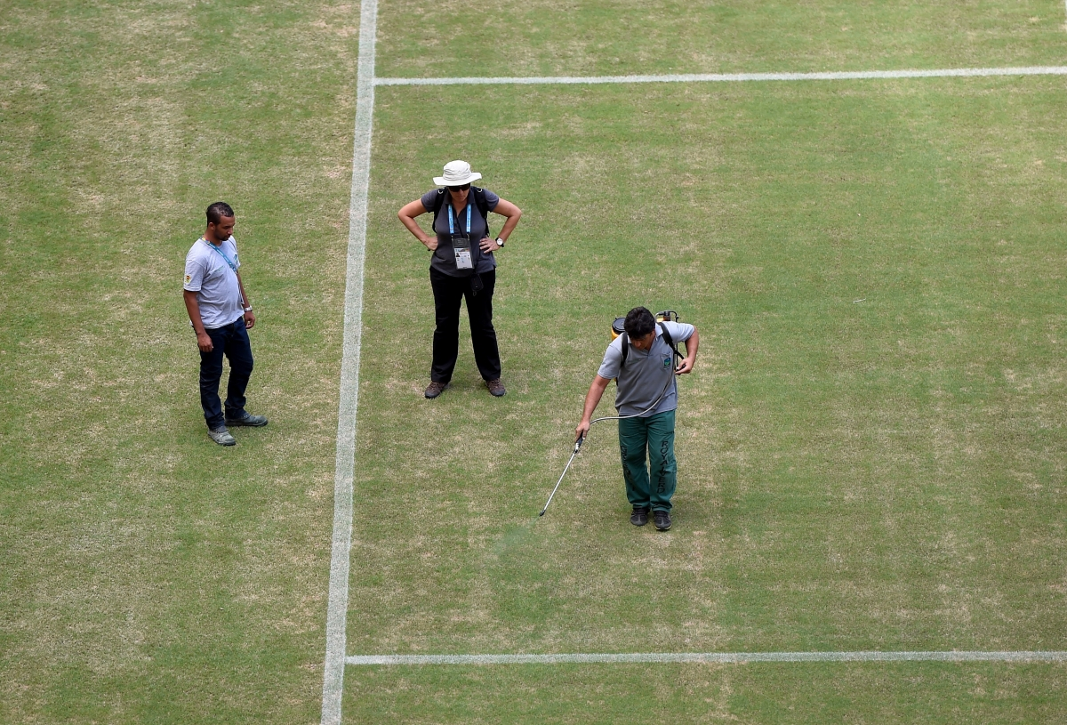 Green paint is sprayed on the parched pitch to improve its colour at Manaus Stadium, ahead of England vs Italy tomorrow