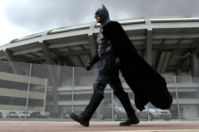 Batman joins a protest near the former site of the Museum of the Indian outside Maracana stadium on December 17, 2013, as firefighters attempted to remove an indigenous man who spent more than 26 hours in a tree to protest against the demolition of the si