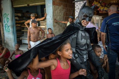 Children throng around Eron Morais de Melo, disguised as Batman, at the Favela do Metro slum area near the Maracana stadium in Rio on January 9, 2014. Families living in this shantytown were refusing to have their homes demolished as part of a project to