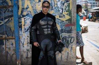 Eron Morais de Melo, a dental technician,  poses for a photograph in his self-made costume at the entrance to the Metro favela in Rio on January 10, 2014