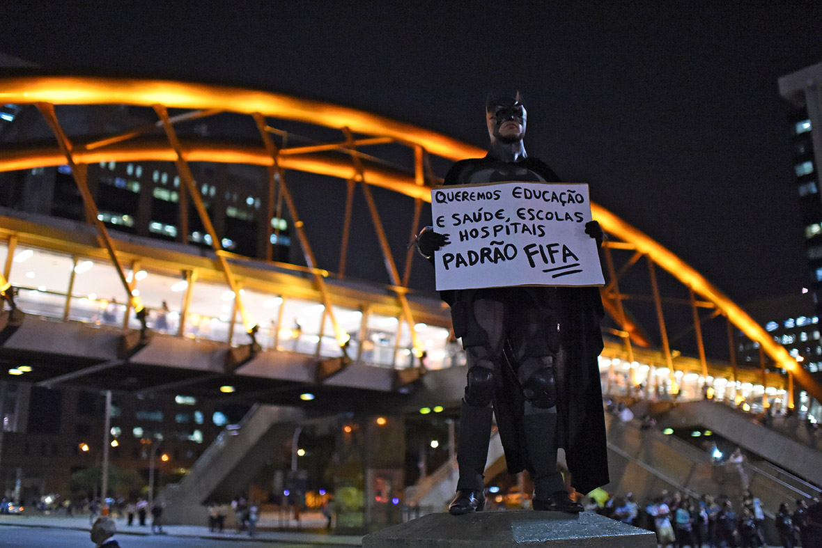 The Dark Knight holds a placard reading