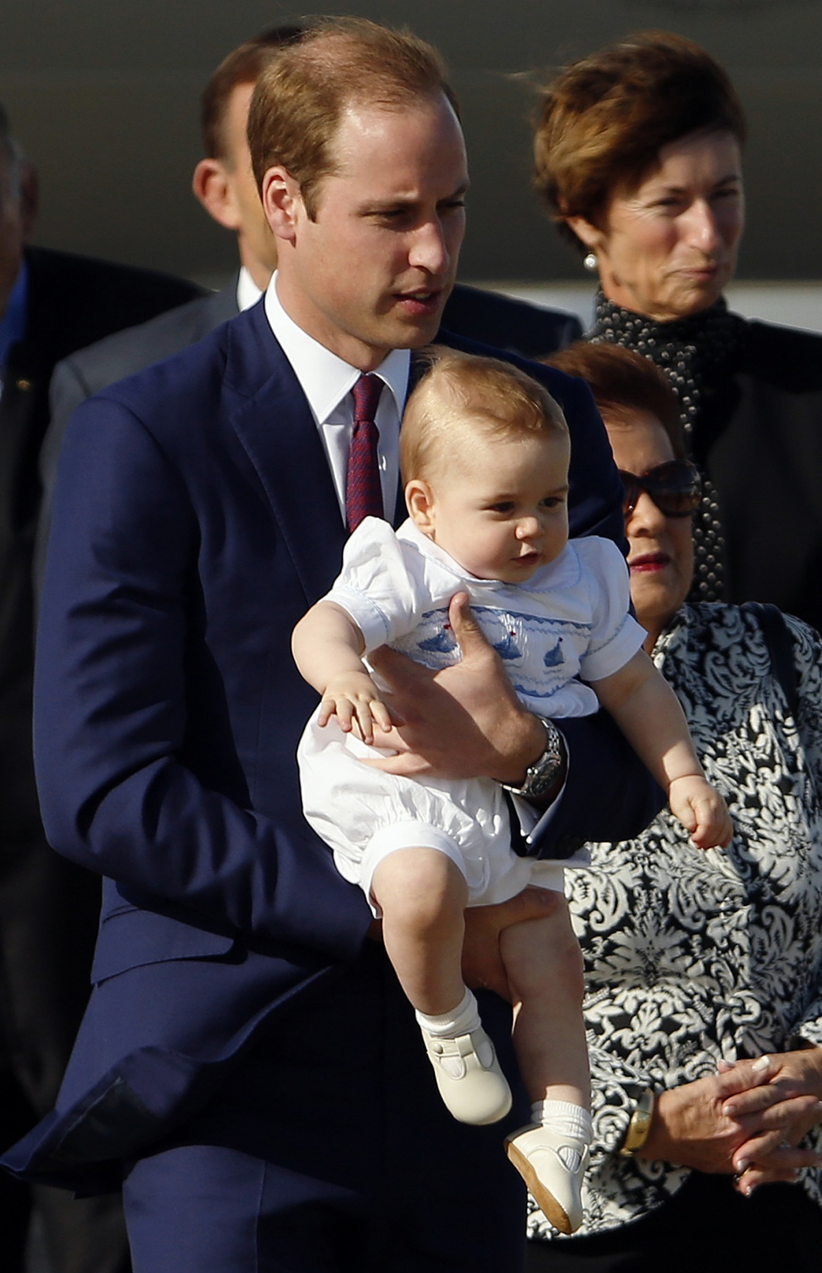 Prince William carries his son Prince George next to officials as he arrives with his wife Catherine, the Duchess of Cambridge, at Sydney Airport April 16, 2014.