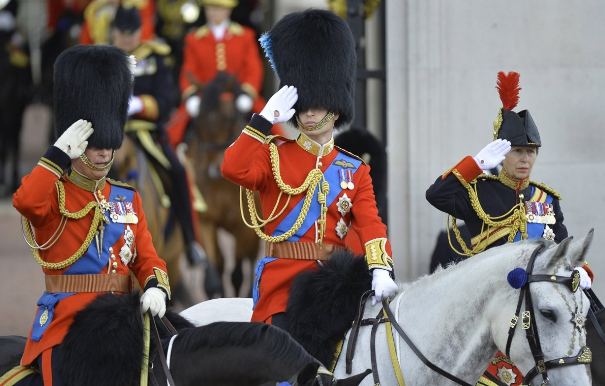 Britain's Prince William, Duke of Cambridge (C), Prince Charles (L) and Princess Anne (R) salute on horseback as they depart Buckingham Palace in the annual Trooping of Colour ceremony
