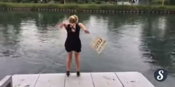 A woman launches herself into the water taking part in l'eau ou l'resto dare. (YouTube)