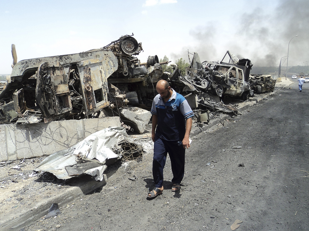 A man walks past near remains of burnt vehicles belonging to Iraqi security forces in the northern Iraq city of Mosul