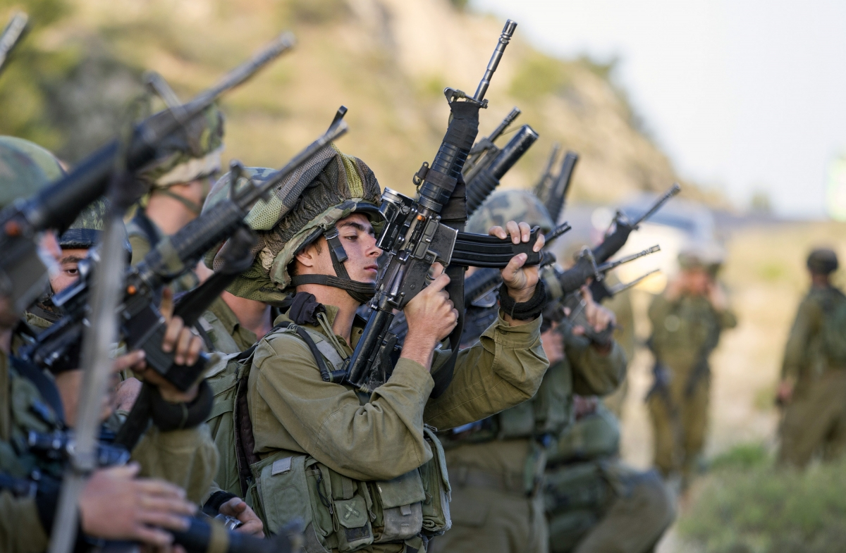 Israeli soldiers load their weapons before taking part in an operation to locate three Israeli teens near the West Bank City of Hebron