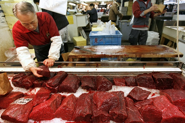 A wholesaler prepares to sell whale meat at the Tsukiji fish market in Tokyo December 12, 2006.