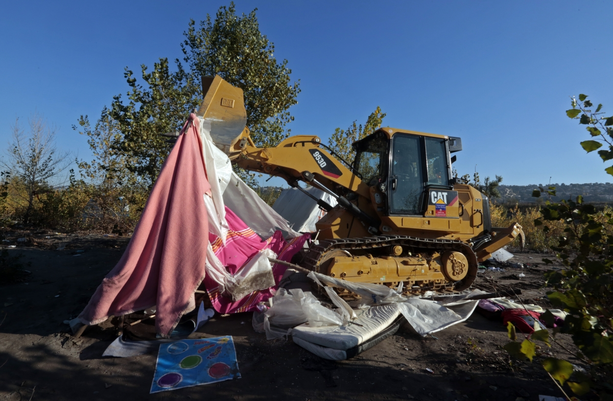 A digger clears the site after the eviction of Roma families from their illegal camp near the bank of the Var river in Nice, southeastern France