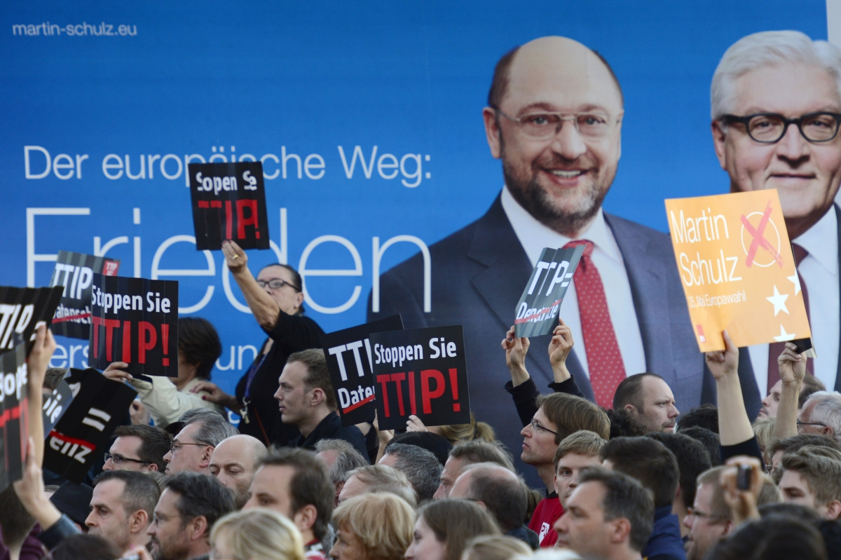 Protesters demonstrating against the Transatlantic Trade and Investment Partnership TTIP hold up signs in front of a placard picturing German Foreign Minister Frank-Walter Steinmeier.