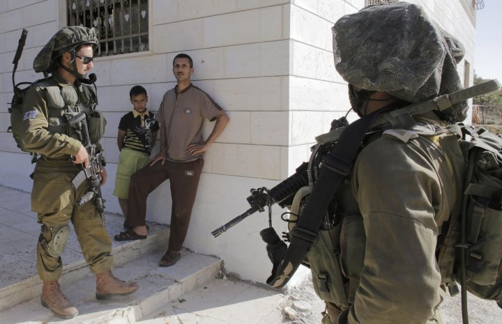 Israeli soldiers stand guard next to Palestinians standing outside their house during an operation to locate three Israeli teens near the West Bank City of Hebron