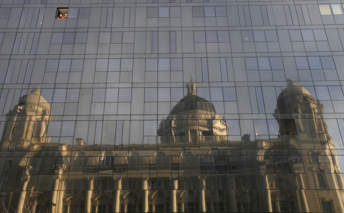 Workmen look out of a window in the new Mann Island apartment development as the Port of Liverpool building is reflected in the glass, in Liverpool, northern England February 14, 2011.