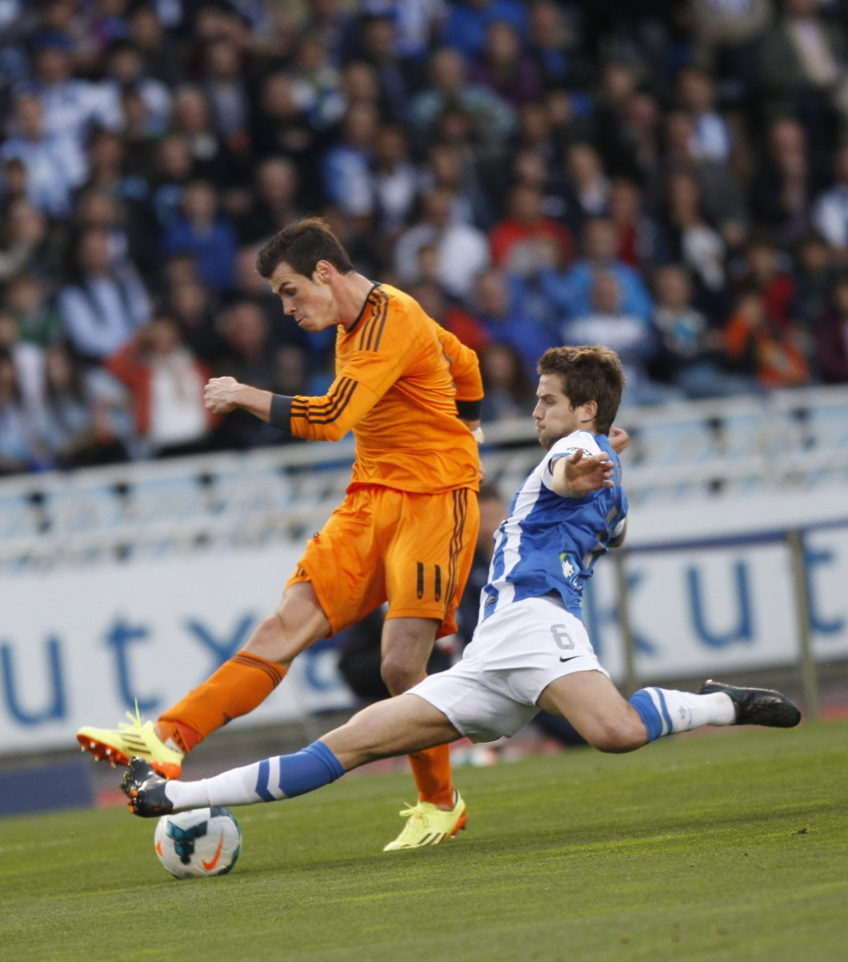 Real Madrid's Gareth Bale fights for the ball with Real Sociedad's Inigo Martinez during their La Liga soccer match at Anoeta stadium in San Sebastian April 5, 2014