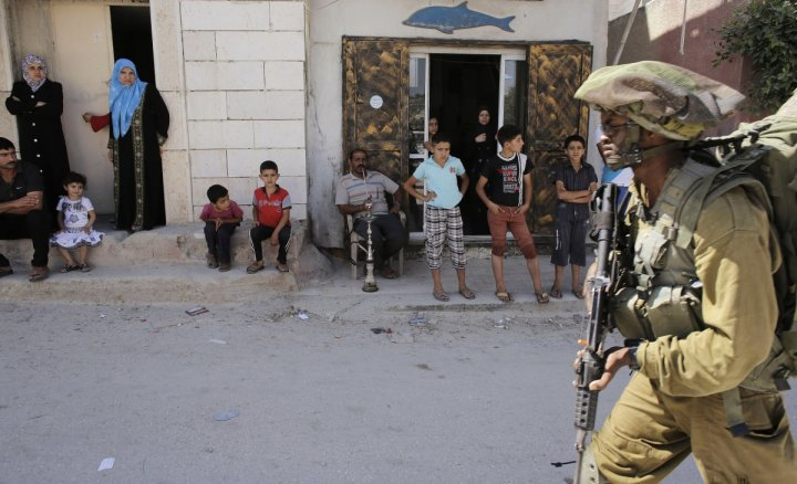 Palestinians watch as an Israeli soldier patrols near the West Bank City of Hebron